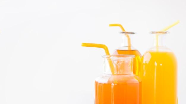 Gros plan, de, a, oranges, et, jus mangue, bouteilles, à, boire, pailles, isolé, sur, fond blanc Photo gratuit