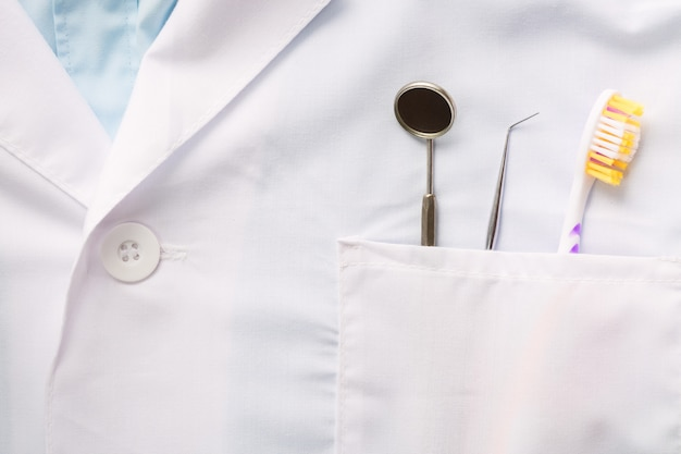 Gros Plan De L'outil Dentaire, Brosse à Dents Et Un Miroir Dans La Poche D'uniforme Médical Blanc. Photo Premium