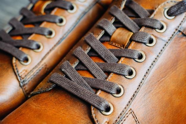 Gros plan d'une paire de chaussures en cuir marron pour hommes. laçage sur les chaussures Photo Premium