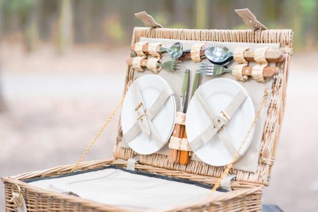 Gros plan d'un panier de pique-nique ouvert sur une table en bois dans le parc. Photo Premium