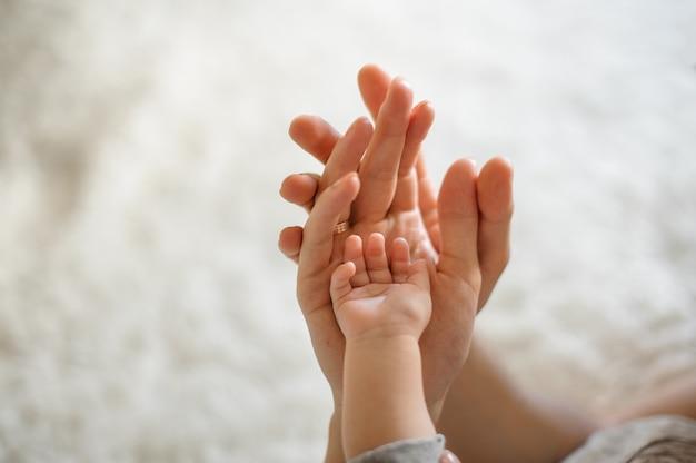Gros Plan Des Parents Et Bébé Joignent Les Mains Photo Premium