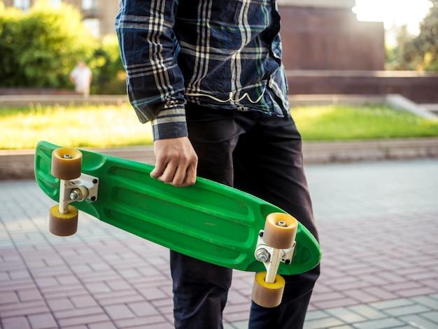 Gros plan sur une partie du corps d'un jeune homme marchant dans la ville avec une nouvelle planche de penny de skateboard moderne Photo Premium