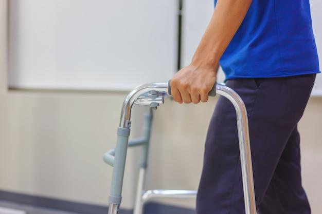 Gros plan, un patient d'âge moyen utilise des marcheurs pour s'exercer à marcher après la chirurgie. Photo Premium