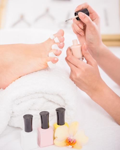Gros plan d'un pédicure appliquant du vernis à ongles sur les ongles des pieds. Photo Premium