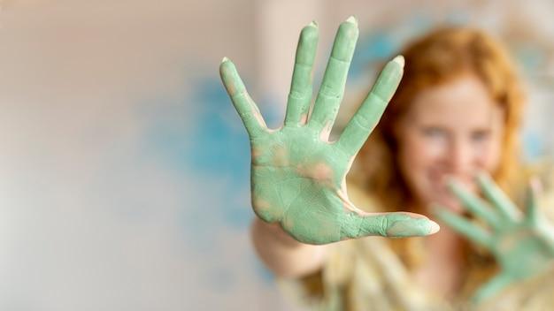 Gros plan de peinture verte sur les paumes de la femme Photo gratuit