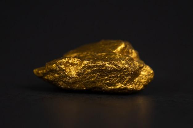 Gros plan de pépite d'or ou de minerai d'or sur fond noir Photo Premium