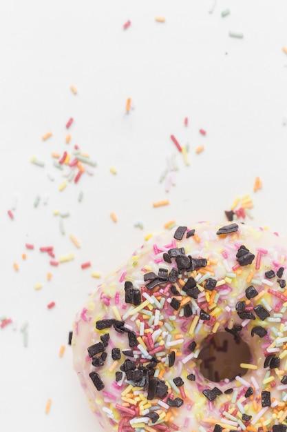 Gros plan de pépites colorées et pépites de chocolat sur le beignet sur fond blanc Photo gratuit