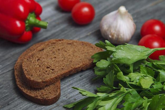 Gros plan de persil sur une table en bois avec des légumes et du pain Photo Premium