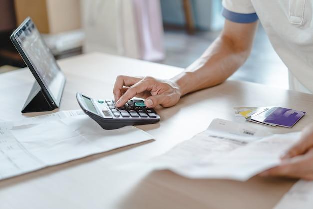 Gros plan personne calculant les dépenses mensuelles et la dette de carte de crédit. Photo Premium