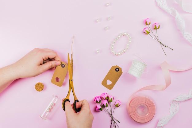Gros plan, personne, coupe, étiquette, bracelet roses artificielles et ruban sur fond rose Photo gratuit