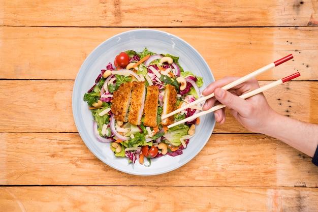Gros plan, de, a, personne, cueillette, nourriture thaï, à, baguettes, sur, bois, bureau Photo gratuit