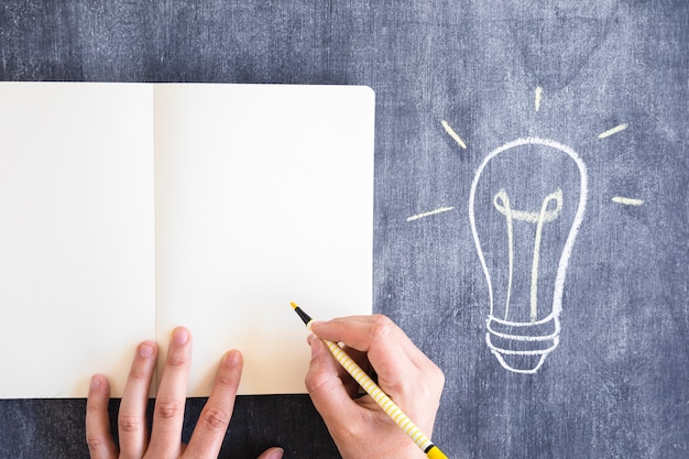 Gros plan, de, a, personne, écriture, à, jaune, feutre, stylo, sur, cahier, contre, tableau Photo gratuit