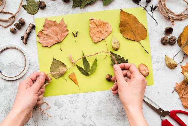 Gros plan, de, personne, main, tenue, ficelle, automne, feuilles, papier vert, contre, toile de fond texturé Photo gratuit