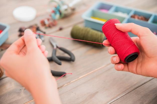 Gros plan, de, personne, main, tenue, fil rouge, bobine, bureau, bois Photo gratuit