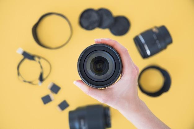 Gros plan, de, personne, main, tenue, lentille appareil photo, sur, accessoires caméra, sur, fond jaune Photo gratuit