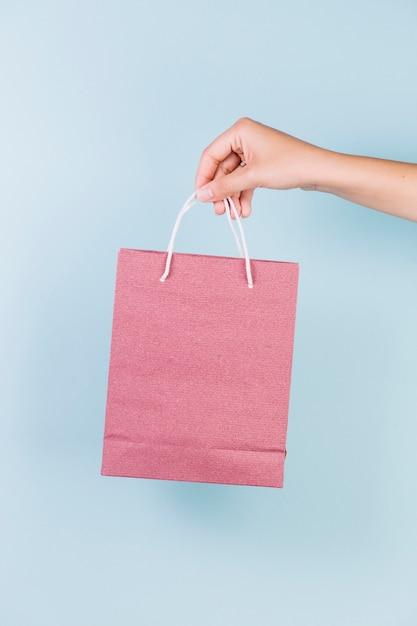 Gros plan, de, a, personne, main, tenue, rose, papier, sac shopping, sur, toile de fond bleu Photo gratuit
