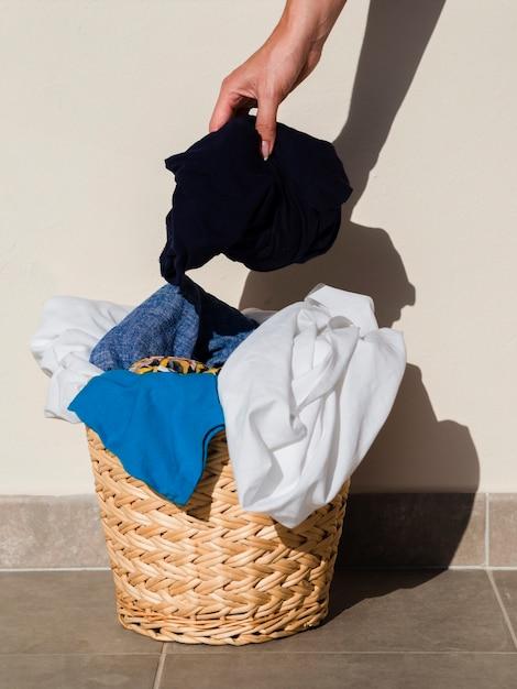Gros plan, personne, mettre, vêtements, panier lessive Photo gratuit