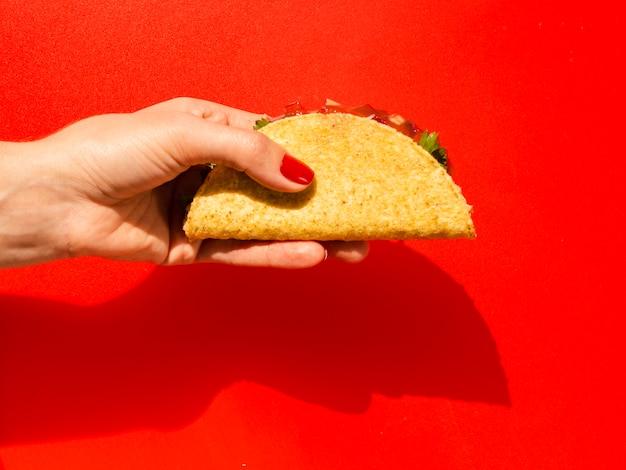 Gros plan personne avec taco et fond rouge Photo gratuit