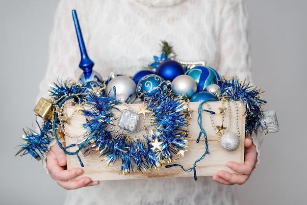Gros Plan D'une Personne Tenant Une Boîte De Décorations De Noël Photo gratuit