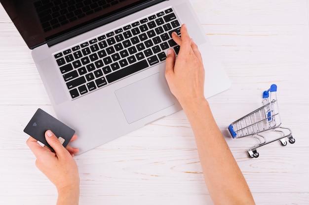 Gros plan, personne, tenue, carte voyages, utilisation, ordinateur portable, et, petite carte commerçante, sur, table bois Photo gratuit