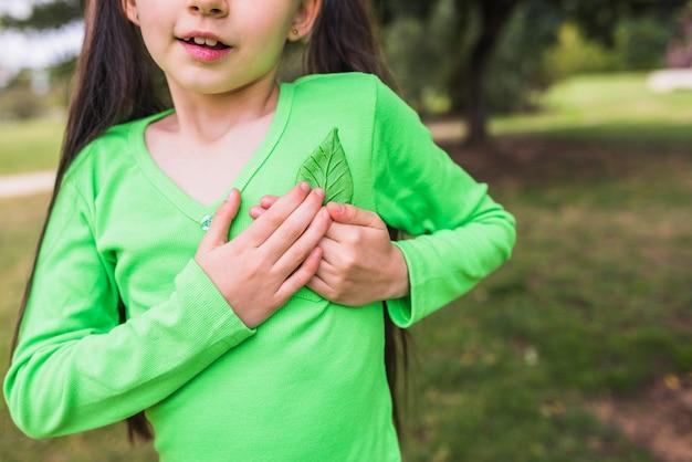Gros plan, petite fille, tenue, faux, feuille verte, près, coeur Photo gratuit