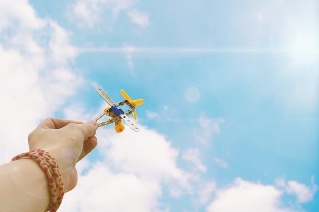Gros plan, photo, main, homme, tenue, jouet, avion, ciel bleu Photo Premium