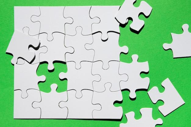 Gros plan, de, pièce puzzle, sur, fond vert Photo gratuit