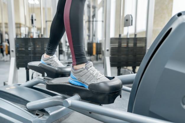 Gros plan des pieds de femme en cours d'exécution sur tapis roulant dans la salle de gym Photo Premium