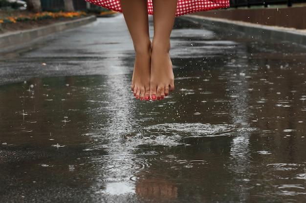 Gros plan des pieds d'une fille dansant dans une flaque après une pluie d'été Photo Premium