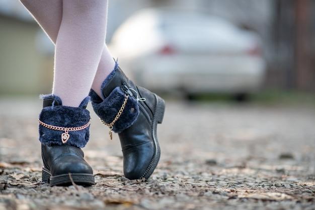 Gros Plan Des Pieds De Fille Enfant En Leggings Roses Et Chaussures D'automne à La Mode Debout à L'extérieur Par Temps D'automne Ensoleillé. Photo Premium