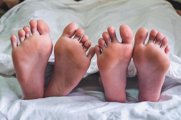 Gros plan des pieds mâles et femelles sur un lit et un couple ayant des relations sexuelles dans la chambre à coucher. Photo Premium