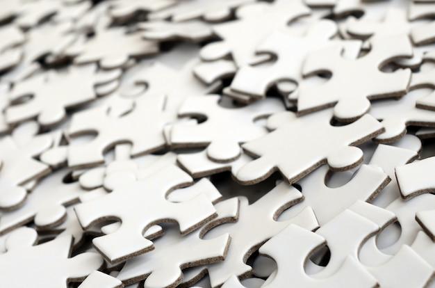 Gros plan d'une pile d'éléments inachevés d'un puzzle blanc. Photo Premium