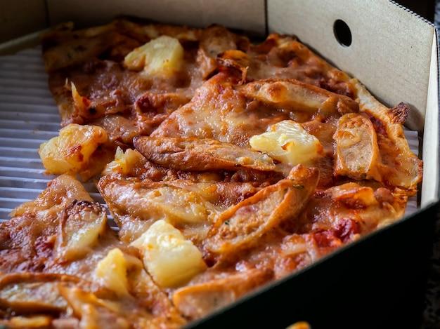 Gros plan d'une pizza fine et croustillante dans une boîte en carton de livraison Photo Premium