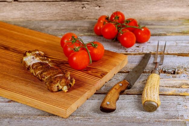 Gros plan sur une planche de bois avec steak de porc grillé à côté de tomates cerises sur table en bois Photo Premium