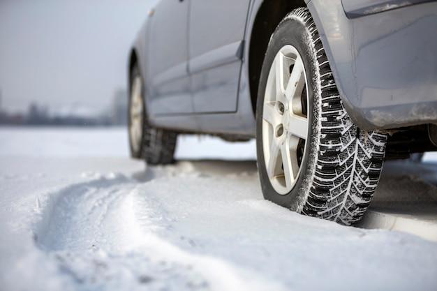 Gros plan d'un pneu de voiture garé sur une route enneigée le jour de l'hiver. concept de transport et de sécurité. Photo Premium