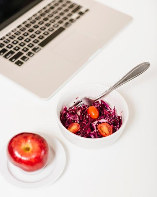 Gros plan, de, pomme, et, ordinateur portable, près, chou rouge, et, tomates, dans, bol Photo gratuit