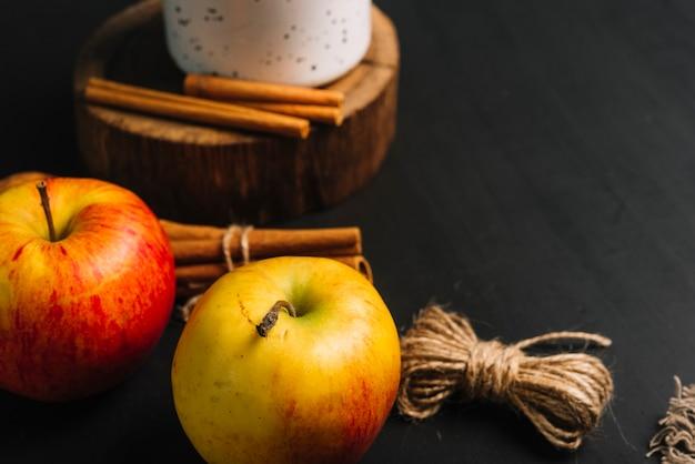 Gros plan et pommes près de la cannelle et de la tasse Photo gratuit