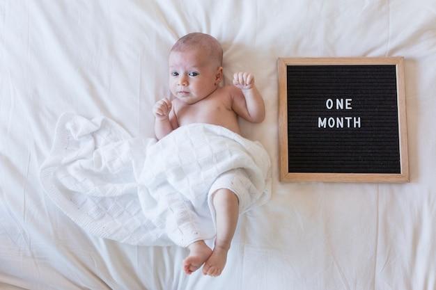 Gros plan le portrait d'un beau bébé sur fond blanc à la maison avec un tableau de lettre vintage avec message: un mois Photo Premium