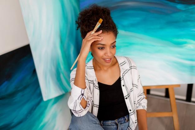Gros Plan Le Portrait D'une Femme Charmante à La Peau Foncée Posant Dans Son Studio D'art Avec Des Peintures Abstraites. Photo gratuit