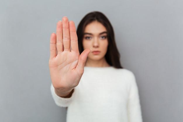 Gros plan le portrait d'une femme montrant le geste d'arrêt Photo gratuit