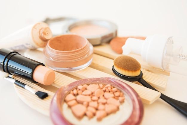 Gros plan d'une poudre de maquillage utilisée dans les cosmétiques d'une femme; brosse; rouge à lèvres et crème Photo gratuit