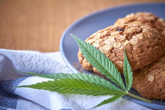 Gros plan de quelques biscuits à la farine d'avoine sur une plaque grise sur une serviette rayée sur une surface en bois claire. Photo Premium