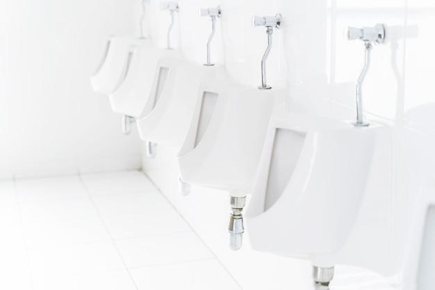 Gros Plan De La Rangée D'urinoirs Dans Les Toilettes Publiques. Photo Premium