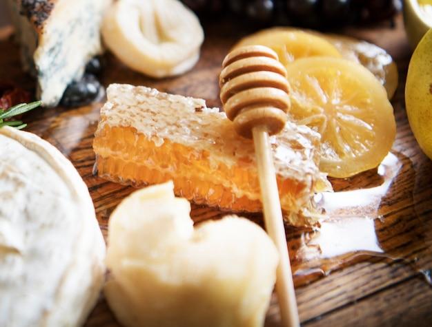 Gros plan d'un rayon de miel sur un plateau de fromages Photo Premium