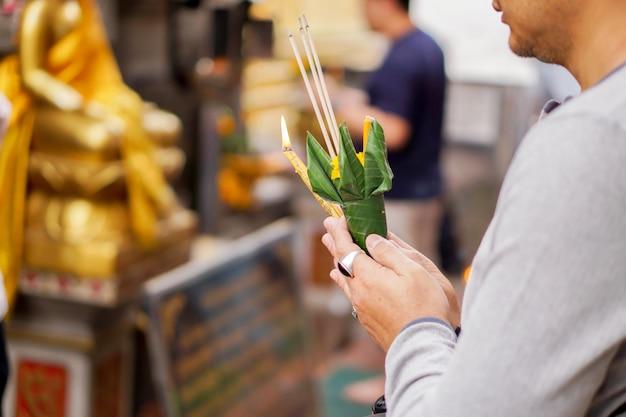 Gros plan et recadrer les mains du jeune homme asiatique tenant un cône d'encens et de fleur Photo Premium