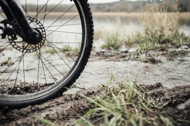 Gros plan, de, roue vélo montagne, dans, les, boue, près, les, lac Photo gratuit