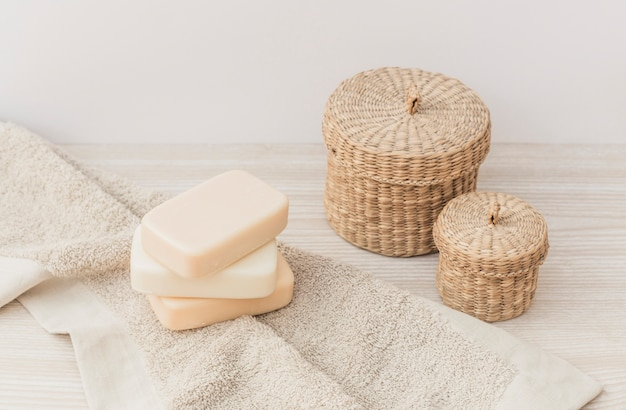 Gros plan des savons; serviette et panier en osier sur une surface en bois Photo gratuit