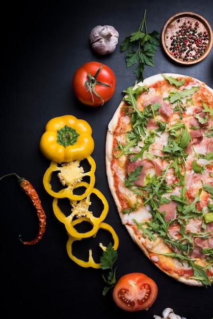 Gros plan d'une savoureuse pizza crue avec des tranches de poivron; tomate; ail; chili et épices sèches Photo gratuit