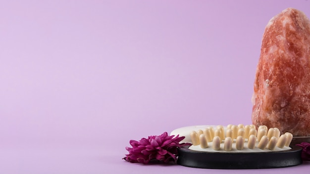 Gros plan, sel rose, rose, himalayen; brosse de massage et fleur sur fond violet Photo gratuit