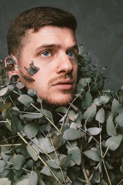 Gros plan, de, a, sérieux, jeune homme, à, percé oreilles, et, nez couvert, à, vert sec, feuilles Photo gratuit